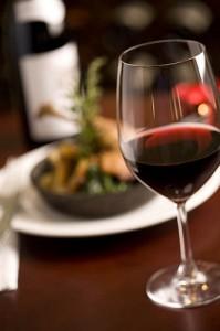 Ein Glas Rotwein im Vordergrund mit Essen im Hintergrund