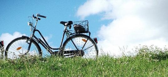 Ein Fahrrad auf einer Wiese mit blauem Himmel